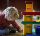 A young boy plays with toys at a playgroup for pre-school aged children.