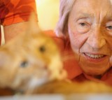 Edith Ehninger, 95, who suffers from dementia, strokes the fur of Mogli during the cat's weekly visit.
