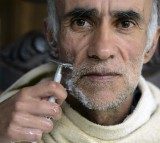 An Alzheimer's patient is shaved by his daughter at his house in Yarumal, north of Antioquia department, Colombia on December 3, 2014.