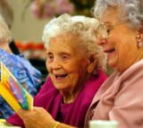 Mamie Underhill (L), 104, and her daughter Leita Chapman laugh while reading a birthday card for Mamie during a birthday celebration for five women residents.