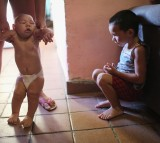 David Henrique Ferreira (L), 5 months, who has microcephaly, is watched by his brother Richard Miguel on January 25, 2016 in Recife, Brazil.