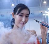 A model smokes an electronic cigarette during the Beijing International Vapor Distribution Alliance Expo.