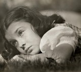 Sad young girl laying on the grass