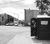 A man coming out of a portable toilet.