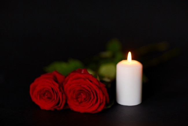 Red roses and burning candle over black background — Stock Image