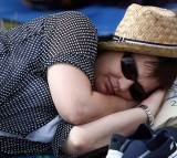 A woman sleeps as she queues up for tickets on day four of the Wimbledon Lawn Tennis Championships.