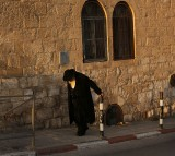 An elderly man walks to the synagogue.