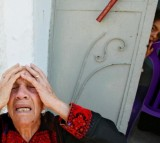 An elderly homeless Palestinian woman, Al-Hajja Fatma, 72, cries while sitting near her home which was destroyed by the Israeli Army in a raid May 26, 2004 in the Gaza Strip.