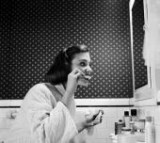 A young woman brushing her teeth in her bathroom.